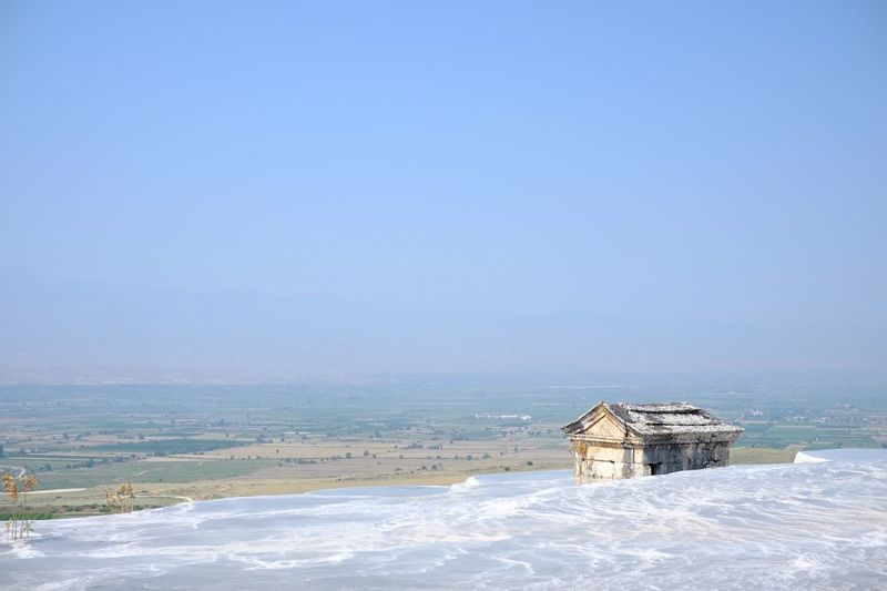 Frozen pools at pamukkale against sky