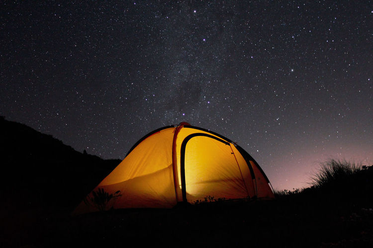 Tent on land against start field during night