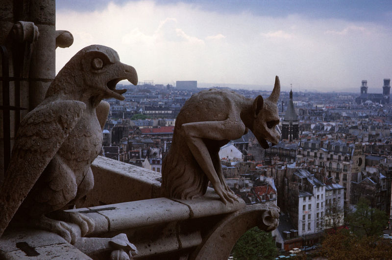 Statues an notre dame  against buildings in city