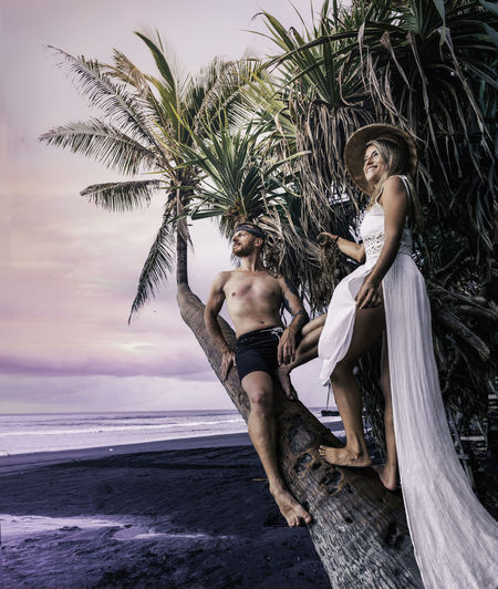 Young couple on palm tree