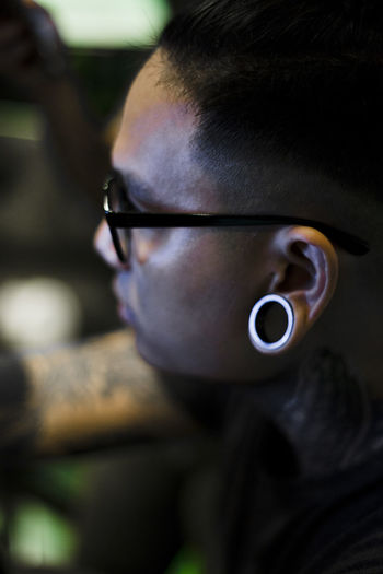 Close-Up Of Man With Eyeglasses And Piercing