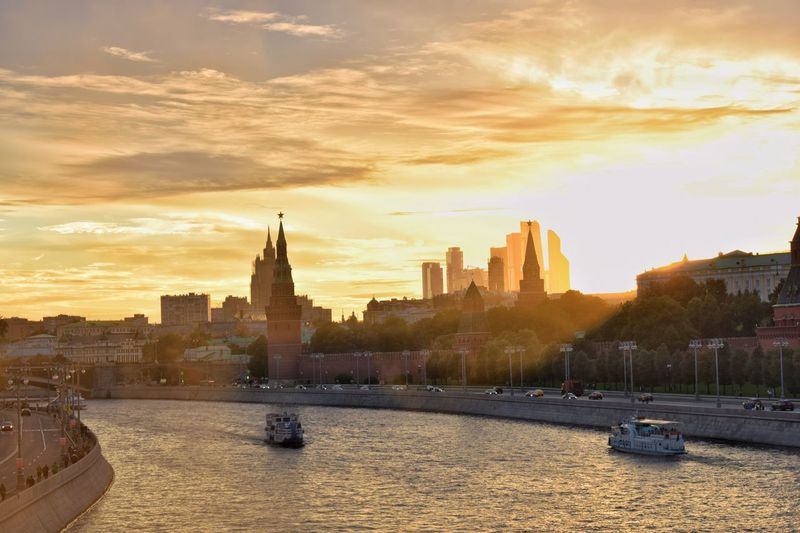 Boats in moskva river by spasskaya tower against cloudy sky during sunset