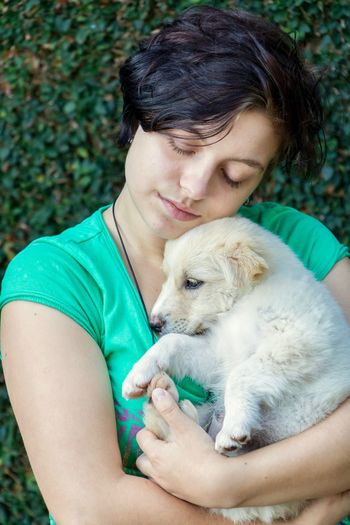 Close-up of teenage girl embracing puppy