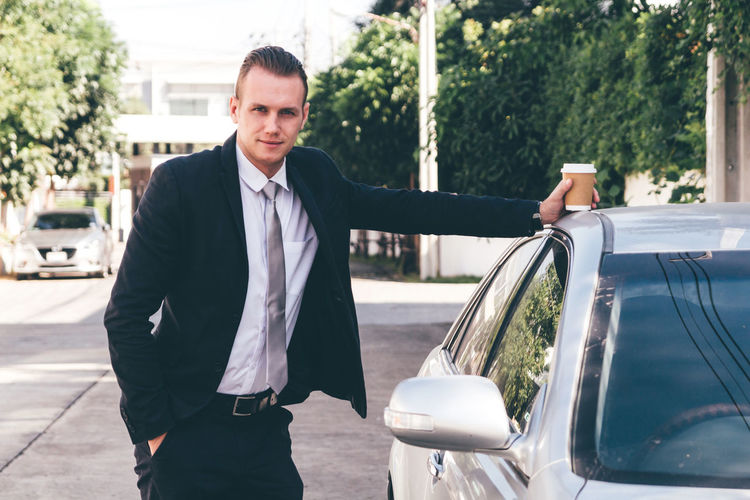 Portrait of businessman standing with car on road