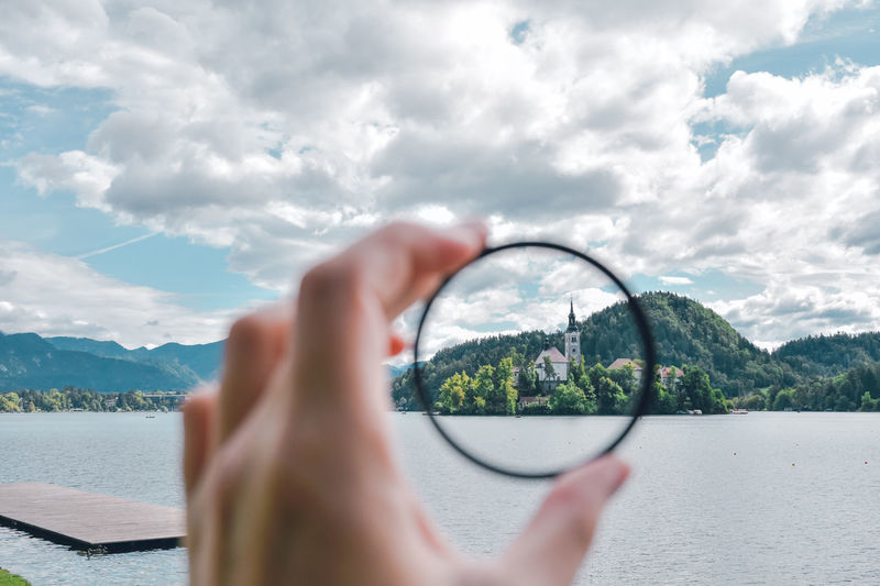 Cropped hand holding circle shaped by lake bled against cloudy sky