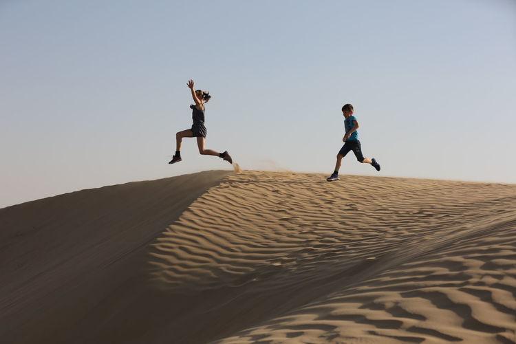 Siblings jumping at desert against clear sky