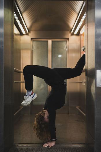 Side view of woman doing handstand at doorway