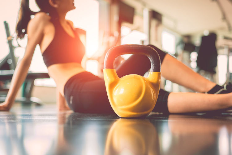 Midsection Of Woman With Kettlebell Sitting In Gym