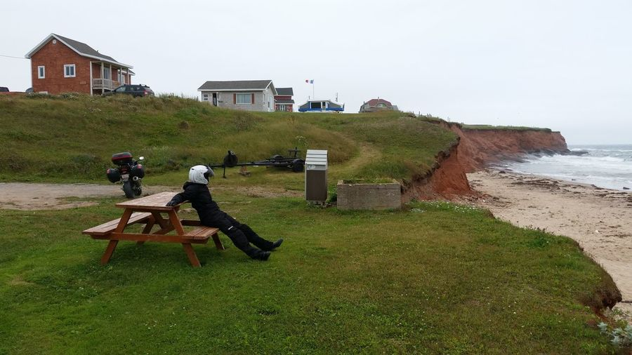 Biker in protective clothing sitting on picnic table by beach