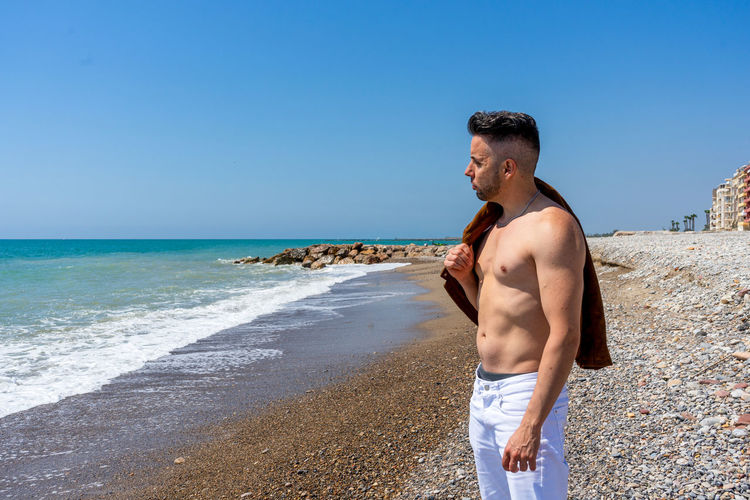 Man standing at beach against clear blue sky