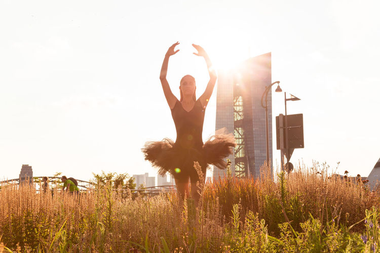 Ballet dancer dancing amidst plants on field against clear sky