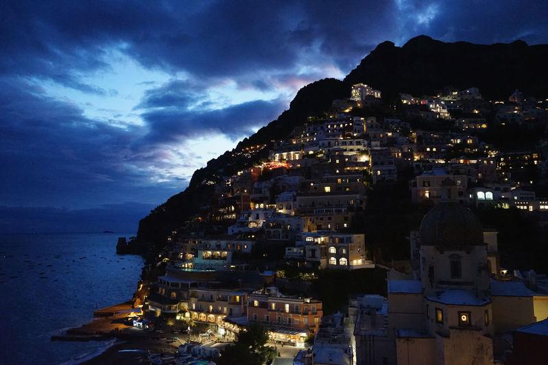 Illuminated houses on mountain by sea against sky at dusk