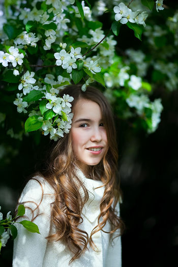 Portrait of cute girl standing by flowering plant outdoor