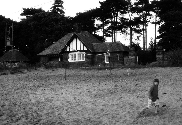Boy on Bawdsey Beach Alone Architecture Bawdsea Beach Suffolk Building Exterior Built Structure Day Grass House In A Row Lawn Leading Narrow Outdoors Residential Structure Roof Running Sand Southwold Suffolk Winter Tuda House Beach Sea Water Inlet Lone Kid On Beach Netbal Net Trees Windswept Windy Foot Prints In The Sand Cold Photographer Photograph Photography Black And White Image Photos Fotos Taking Photos Monochrome Pensive Image Summer The Way Forward Togetherness Tree
