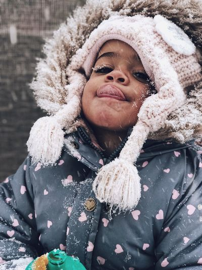 Portrait of child in warm clothing sticking out tongue during snowfall