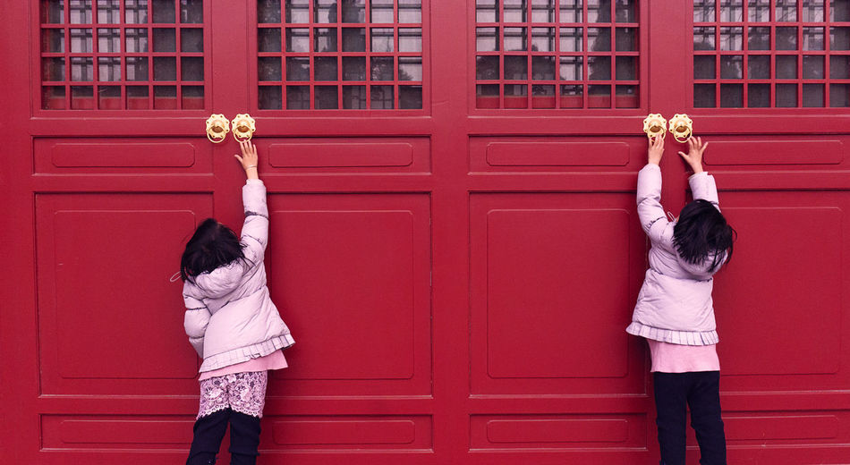 Rear view of girls reaching knobs of red doors