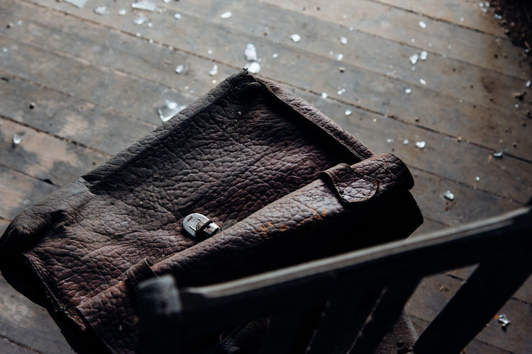 High angle view of weathered leather bag on chair