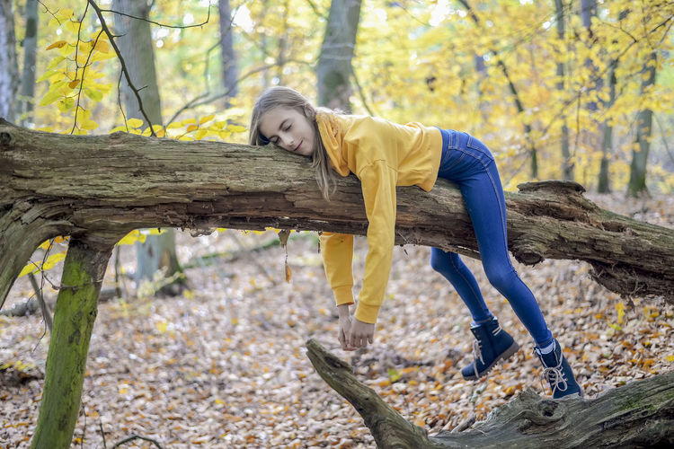 Girl sleeping on tree trunk in forest