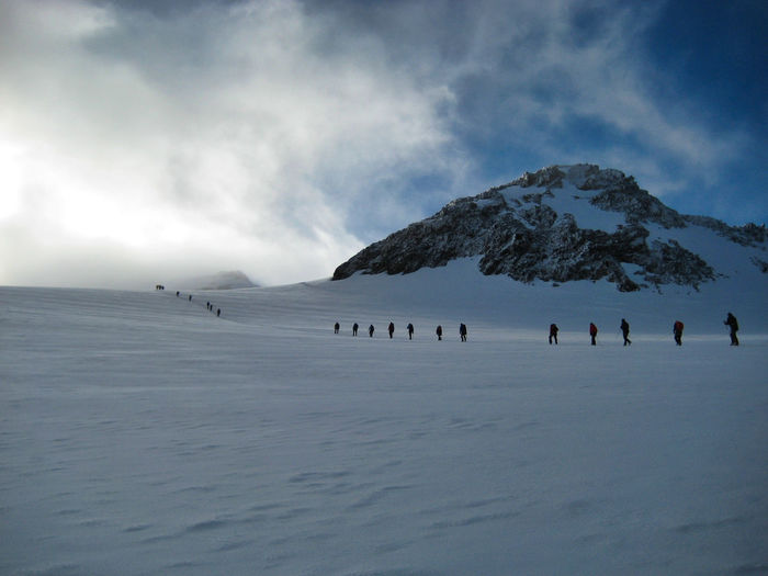 Scenic view of people walking on snow covered mountains against sky