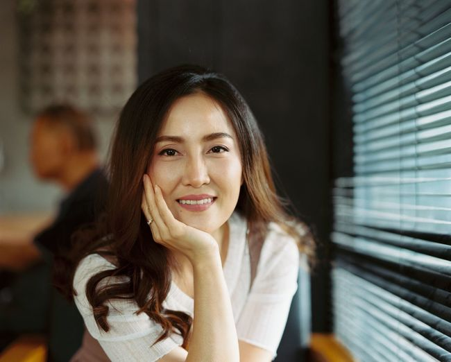 Portrait Of Smiling Mid Adult Woman With Hand On Chin Sitting In Restaurant