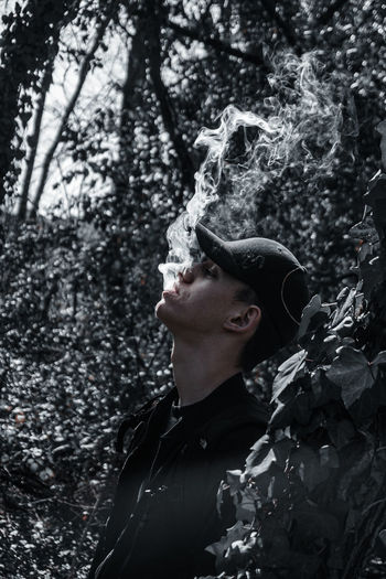 Man exhaling smoke while standing in forest