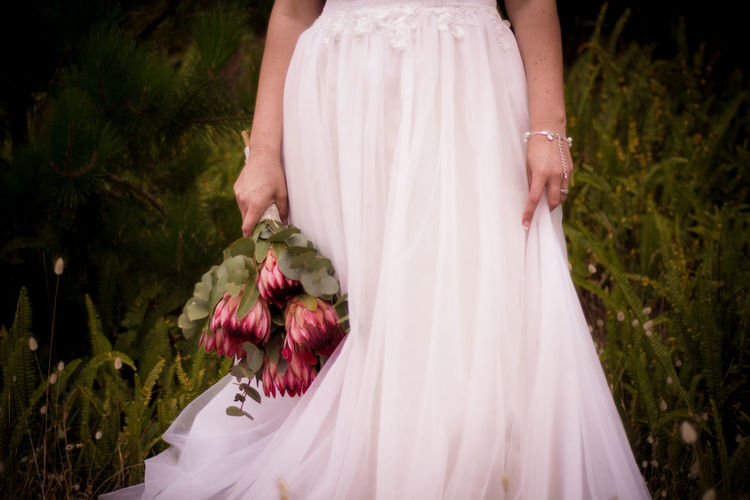 Midsection Of Bride Wearing Wedding Dress Standing On Field