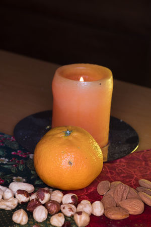 Winter Fruits With Candle Candle Cashew Nuts Nuts Almonds Candle Candle Light Citrus Fruit Clementine Close Up Close-up Dark Background Day Flame Flash Photography Food Freshness Fruit Illuminated Indoors  Indoors  No People Orange - Fruit Orange Color Patchwork Art