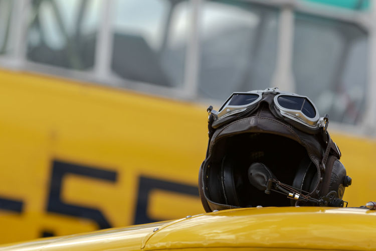 Close-up of crash helmet on vehicle with bus in background