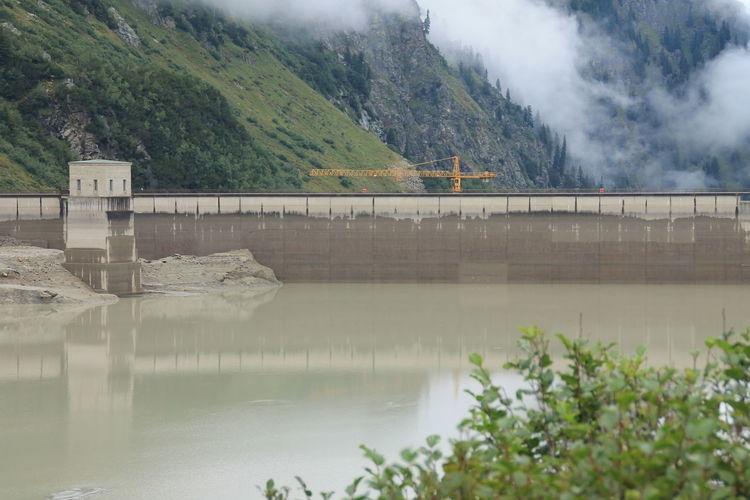 Bridge over calm river against mountain