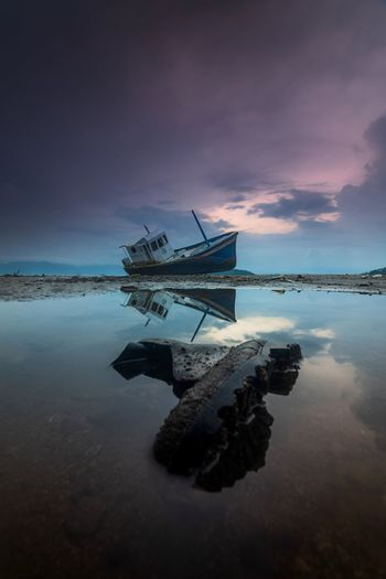 Abandoned ship in sea against sky during sunset