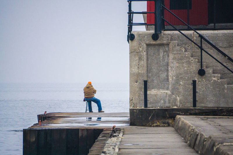 Full length rear view of man sitting on chair at pier