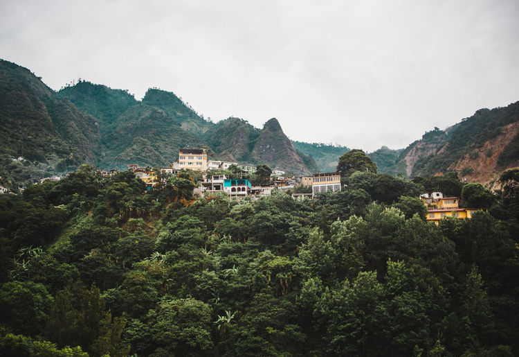Houses by trees and mountains against sky
