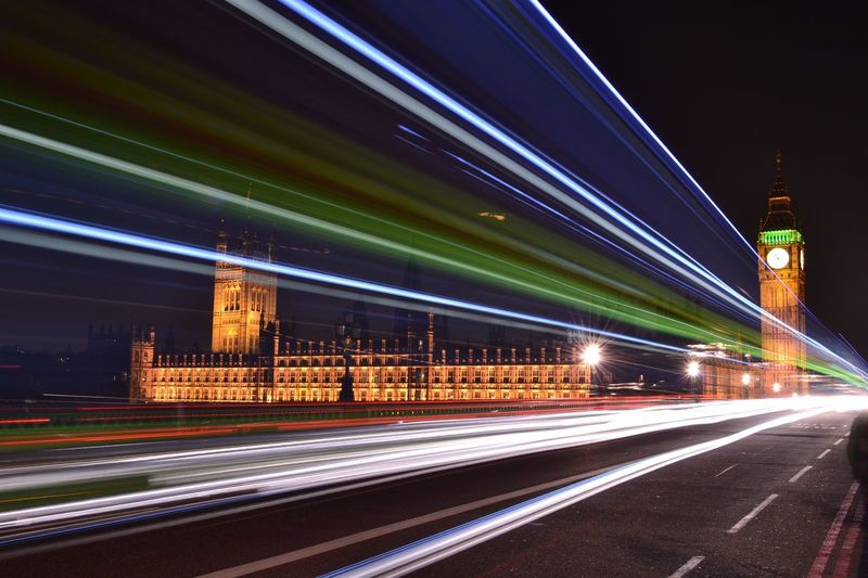 Light trails over street by big ben against sky at night