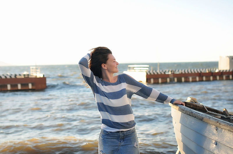 Nice girl curly hair in a striped sweater and a denim skirt with holes stands near an old gray boat