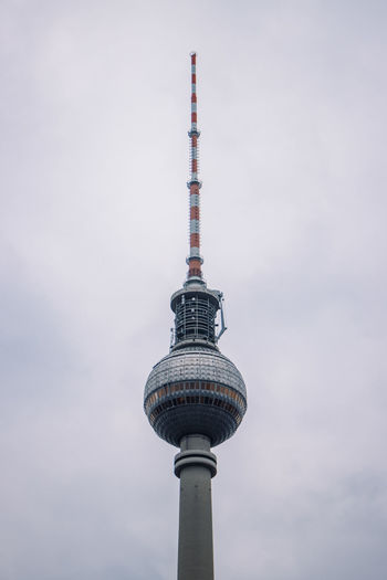 Low angle view of communications tower against sky in city
