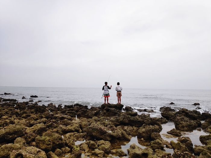 Rear view of boys standing on rocks at sea shore