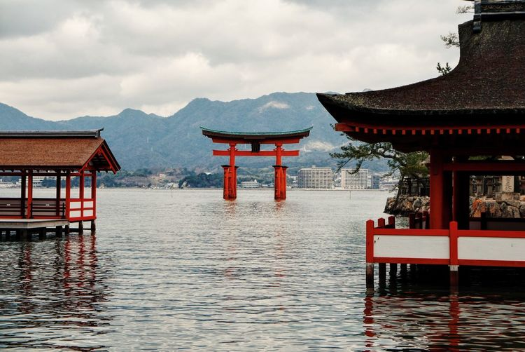 Torii Gate In Sea At Itsukushima Shrine Against Sky