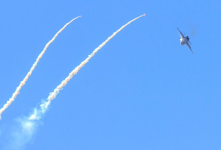 Low Angle View Of Airplanes Flying Against Clear Blue Sky During Airshow