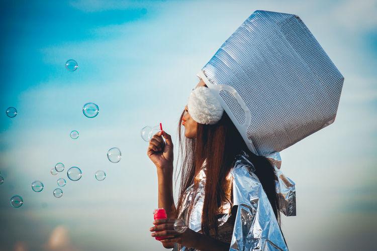 Woman wearing hat blowing bubbles against sky