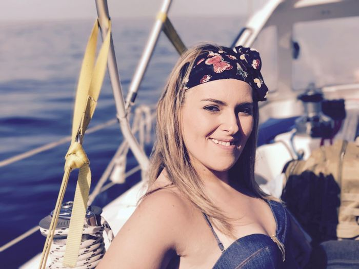 Portrait of smiling beautiful woman on boat in sea