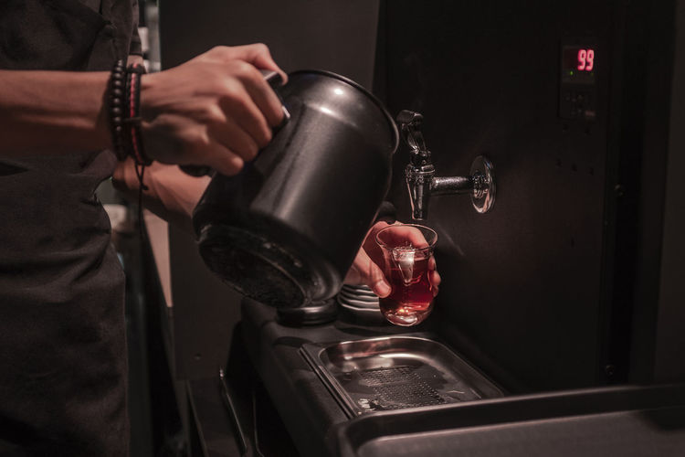 Midsection of man pouring water in coffee at darkroom