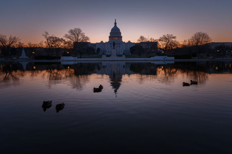 United States Capital Dome With Reflection On River During Sunrise