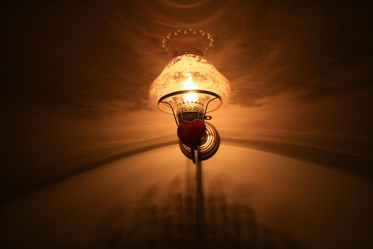 Low Angle View Of Illuminated Light Bulb On Wall In Darkroom