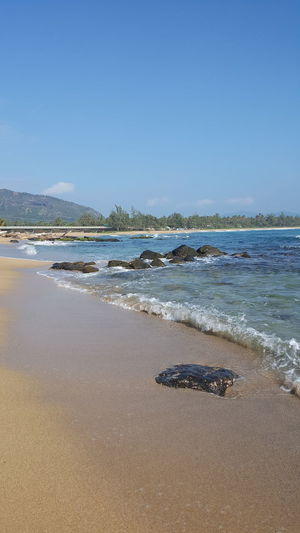 Sea Beach Sand Horizon Over Water Blue Sky Water Wave Nature Clear Sky Outdoors Power In Nature Oceans Lydgate Beach Oceanview Beach Life Serenity And Nature Rocks In Water Beach Photogrqphy Kauai Life Tranquility Travel Destinations Shorelines Beach Walk