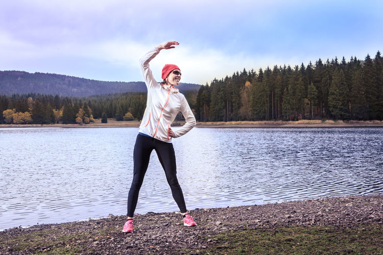 woman running through the forest by the lake Action, Activity, Adult, Autumn, Competition, Female, Fitness. Fit, Forest, Green, Healthy, Hill, Jogging, Lake, Landscape, Lifestyles, Morning, Mountain, Nature, People, Power, Running, Sports, Training, Trees, Water, Woman, Woods Adult Arms Raised Beauty In Nature Day Full Length Human Arm Lake Leisure Activity Lifestyles Nature Non-urban Scene One Person Outdoors Real People Scenics - Nature Sky Standing Tree Water Women Young Adult