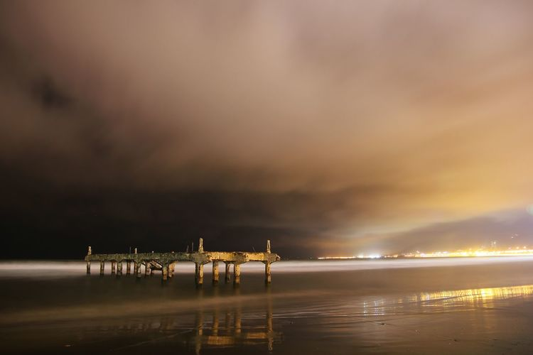 Damaged pier against cloudy sky at beach during night