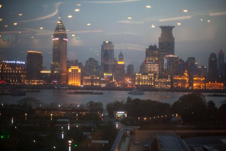 Illuminated Bund Center And Chrysler Building Seen Through Glass Window