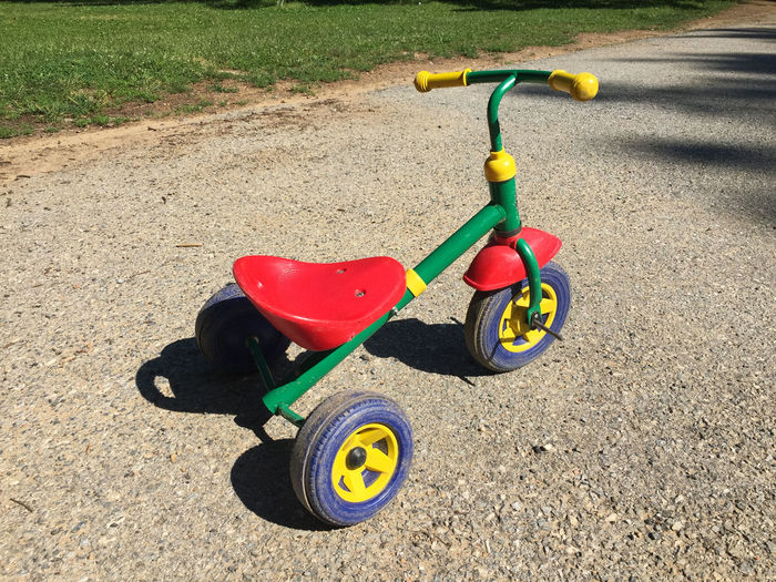 Childhood Day Grass Green Color Land Vehicle Multi Colored No People Outdoors Parking Playground Road Sport Stationary Toy Tricycle Trike Yellow