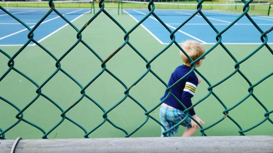 Rear view of boy running on playing field seen through chainlink fence