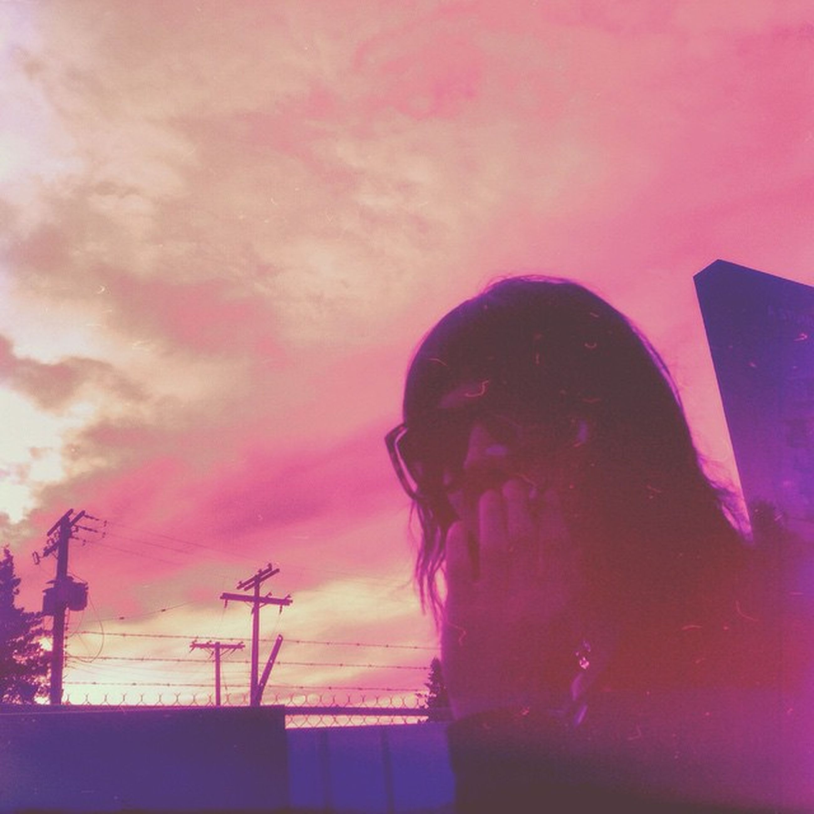 sky, low angle view, lifestyles, silhouette, leisure activity, cloud - sky, sunset, built structure, architecture, building exterior, dusk, standing, outdoors, waist up, cloud, three quarter length, technology, headshot
